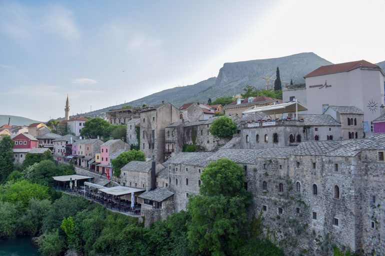 stone and colourful buildings on mostar along river things to do in mostar