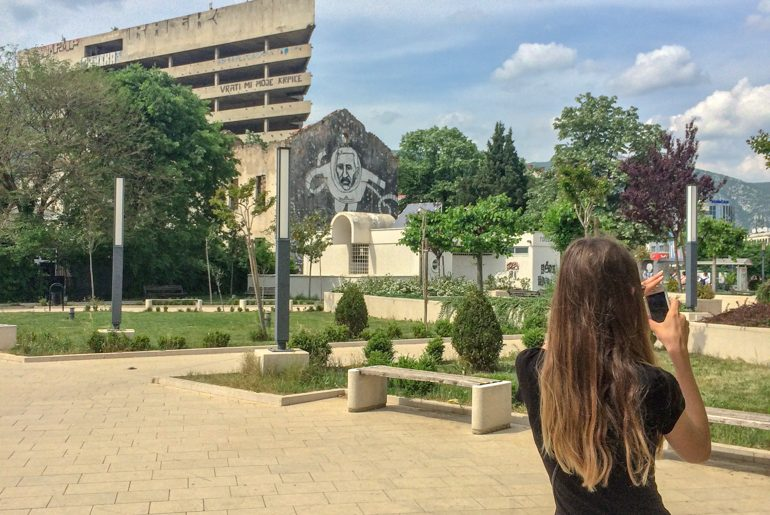 girl taking photo in green square with buildings behind things to do in mostar