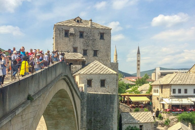 stari most mostar bridge filled with people and blue sky things to do in mostar