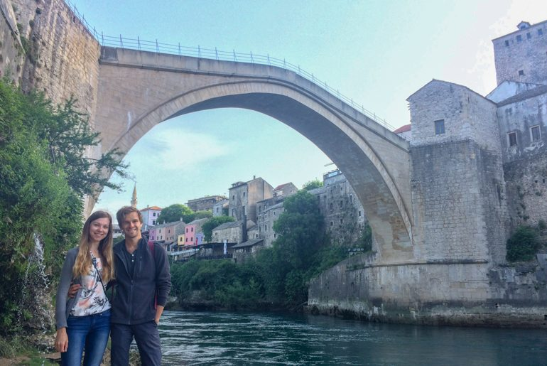 young couple posing under old bridge in mostar with river behind things to do in mostar