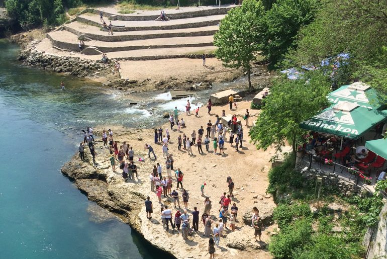 people taking photos down below by blue river in mostar things to do in mostar bosnia