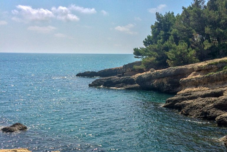 blue water with rocks and green trees in cove things to do in ulcinj