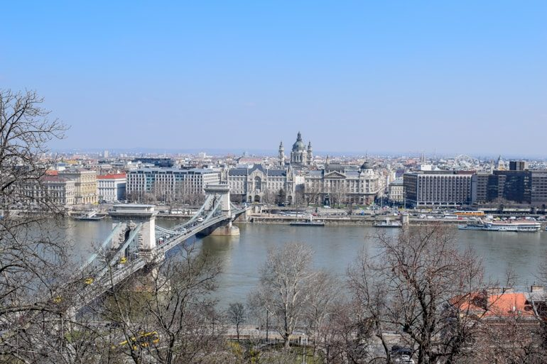 cathedral and chain bridge through trees in budapest best areas to stay