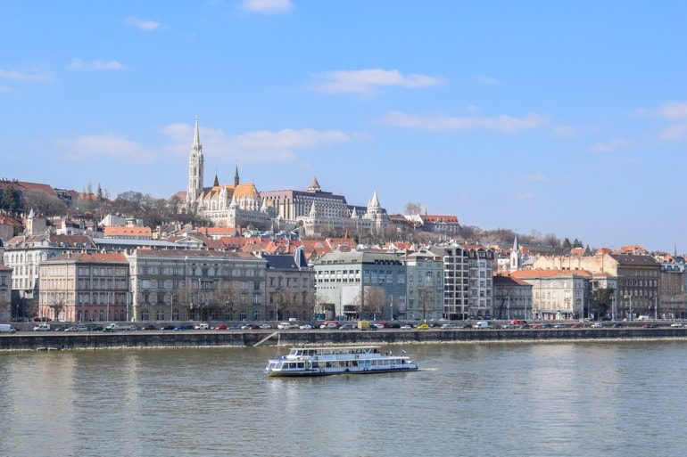 boat in danube river crossing in front of church and buildings in budapest best areas to stay