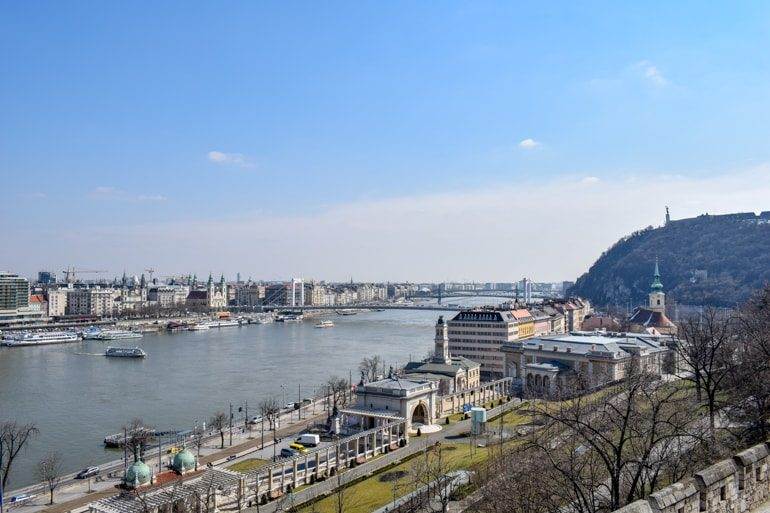Danube river with hill and buildings lining in budapest best areas to stay