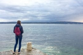 girl with purple backpack standing on rocky pier with blue sea behind best travel gadgets for backpackers