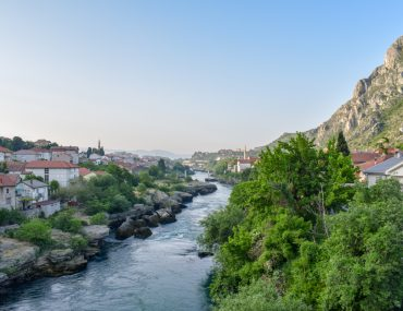 blue river with green trees and old houses on river bank in mostar bosnia and herzegovina travel