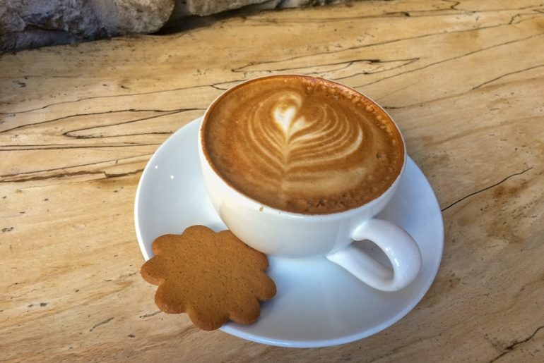 latte in white mug and cookie on wooden table with rock wall coffee shops in edinburgh