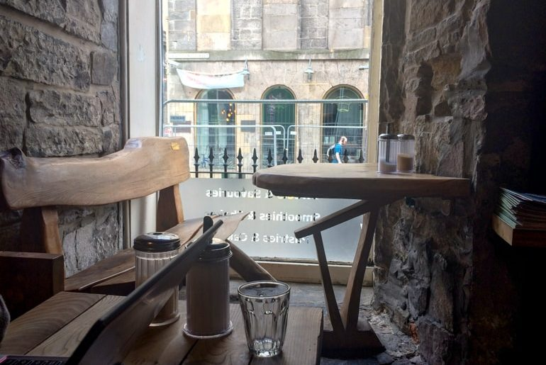 wooden bench and table with bright window at coffee shop in edinburgh black medicine