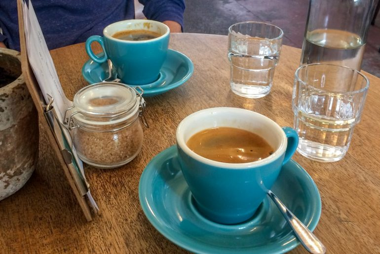 blue mugs and water glasses with menu on wooden table in coffee shop in edinburgh