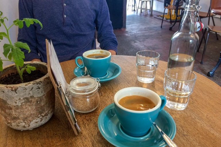 turquoise mugs and water glasses with menu on wooden table with green plant in coffee shop in edinburgh