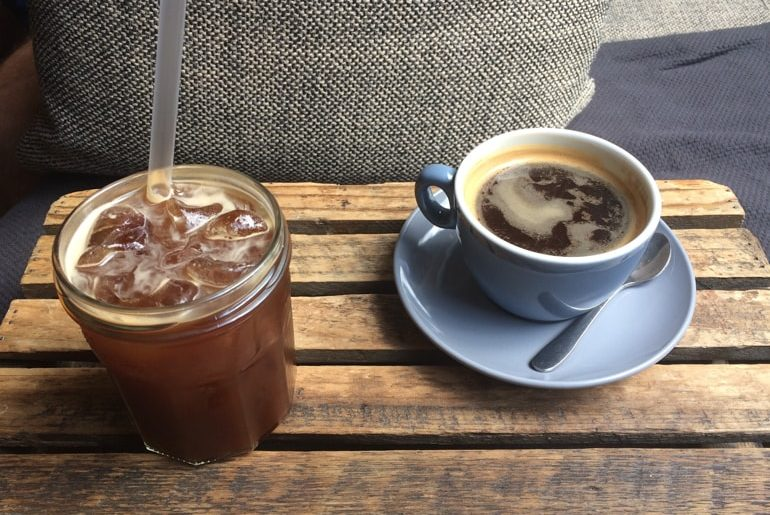 cold coffee in glass and coffee in blue mug on wooden crate in milkman coffee shops edinburgh