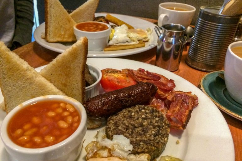 full scottish breakfast with beans and toast and coffee in coffee shop in edinburgh