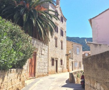 sandstone streets in with colourful houses and blue sky on croatia road trip