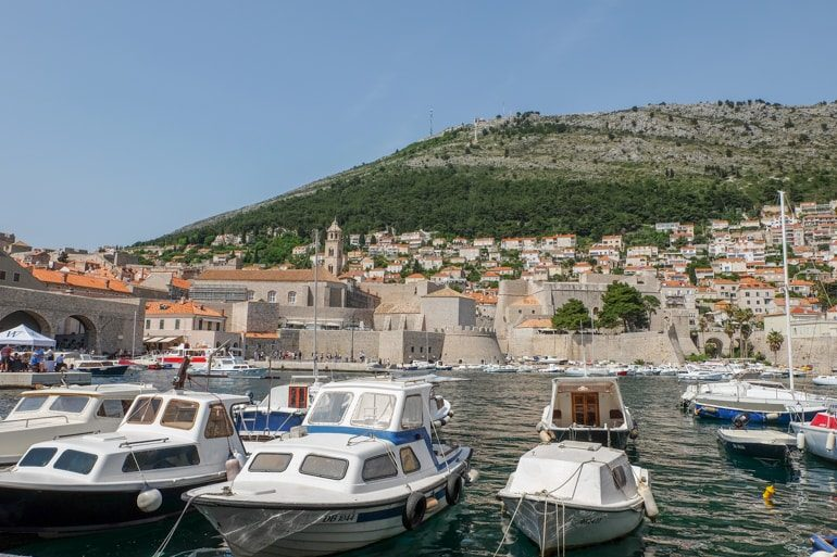 boats in dubrovnik harbour with hill in behind on croatia road trip