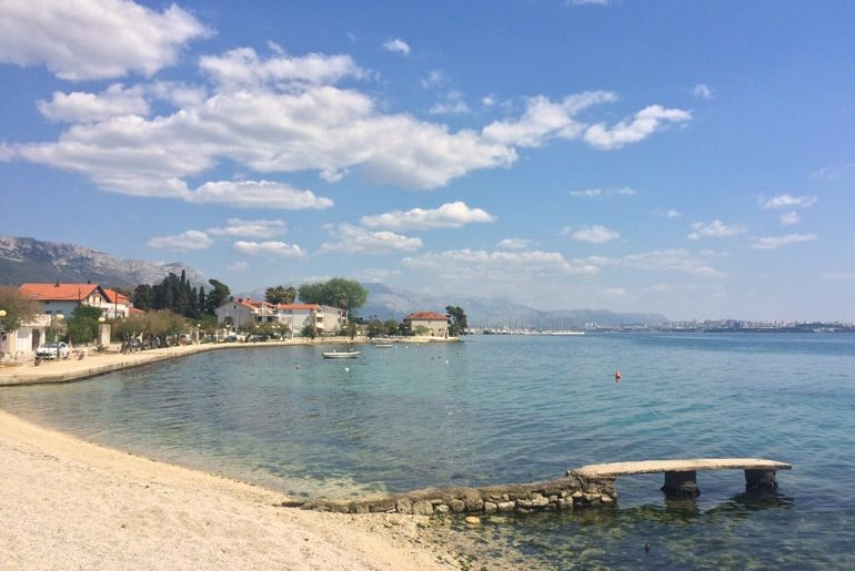 rocky beach with sidewalk and little dock in blue sea croatia road trip