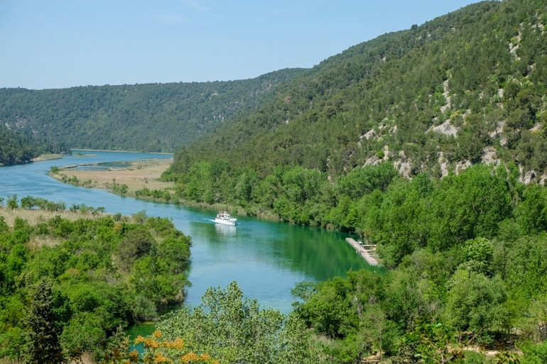 ferry on blue water through green trees in krka national park on croatia road trip
