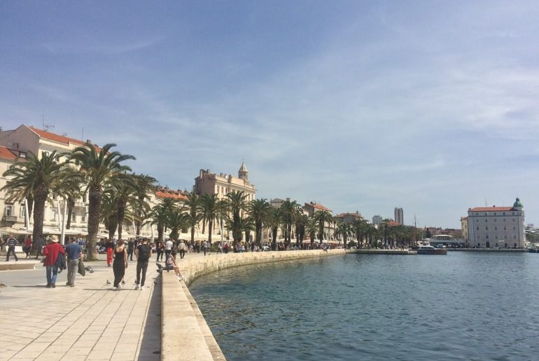 walkway with shoreline and palm trees in split croatia road trip