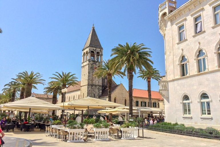 church tower with cafe umbrellas in trogir croatia road trip