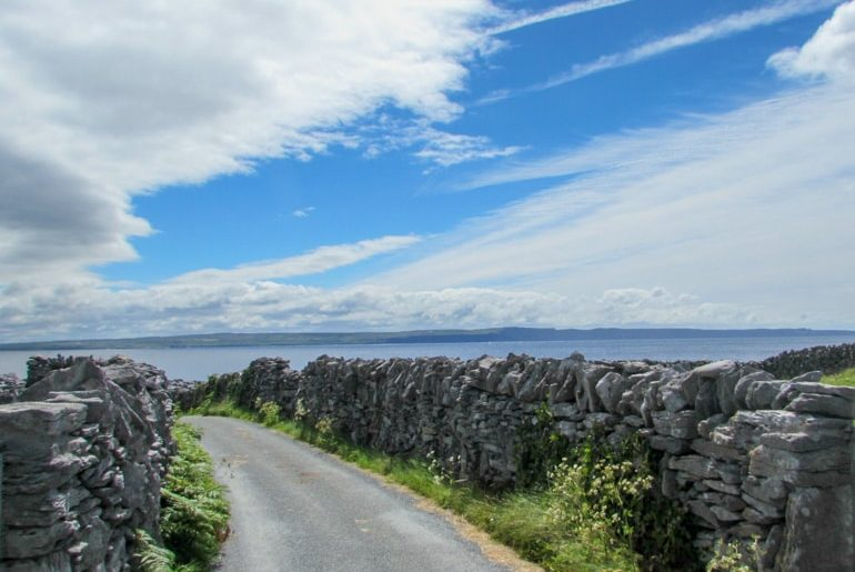 road with stone wall along it and blue sky ireland travel tips