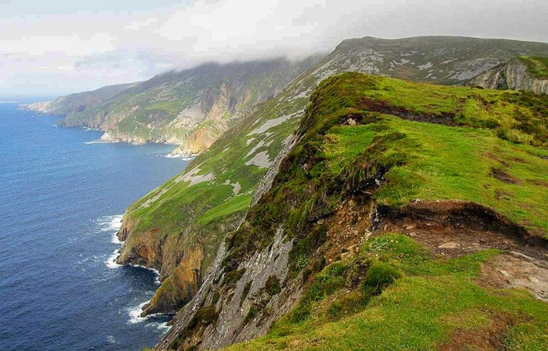 green rocky cliffs with blue water below slieve league cliffs ireland travel tips