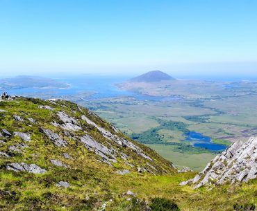 green rolling rocky mountains with blue sky ireland travel tips