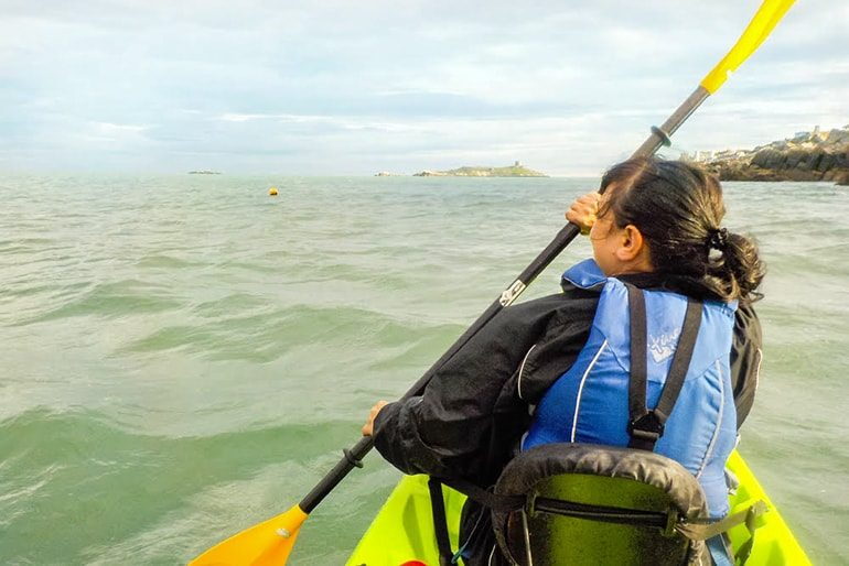 woman kayaking with paddle in green sea ireland travel tips