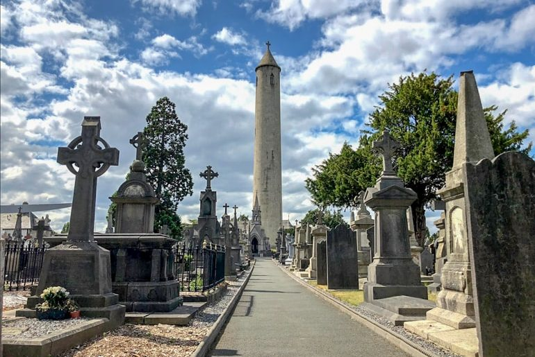 tombstones in cemetery with straight path and tower ahead ireland travel tips