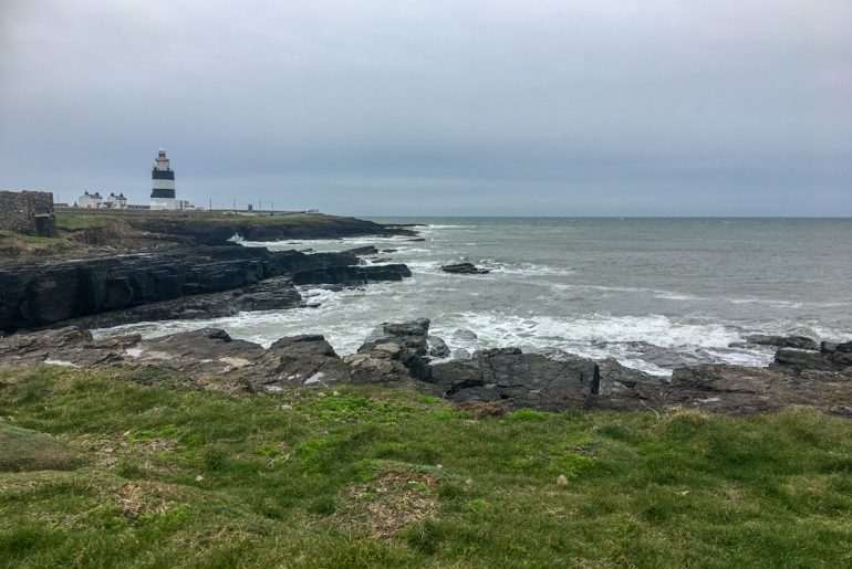 lighthouse and wavy shore at hook head peninsula ireland travel tips