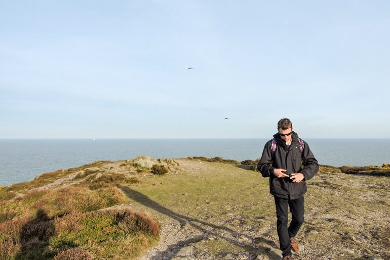 man in black jacket walking away from cliff edge in ireland travel tips