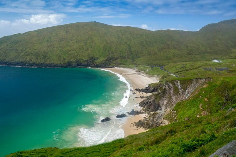 blue water waves and white sand in green bay ireland travel tips