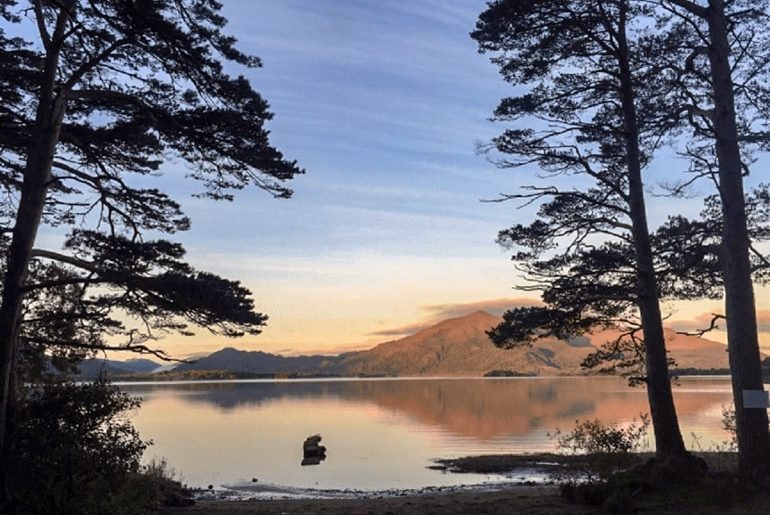 sunset and red trees with shadows on calm water at killarney national park ireland travel tips
