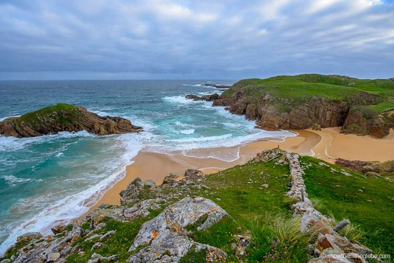 blue water and yellow sand beach with cloudy sky and green hills ireland travel tips