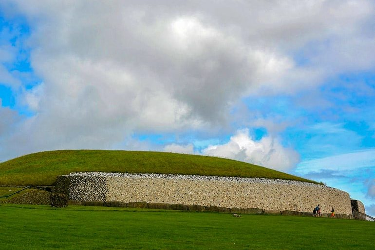 newgrange round stone and green grass monument with cloudy blue sky ireland travel tips