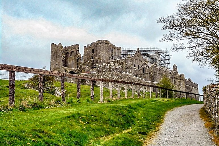 stone castle with lush green grass rock of cashel ireland travel tips