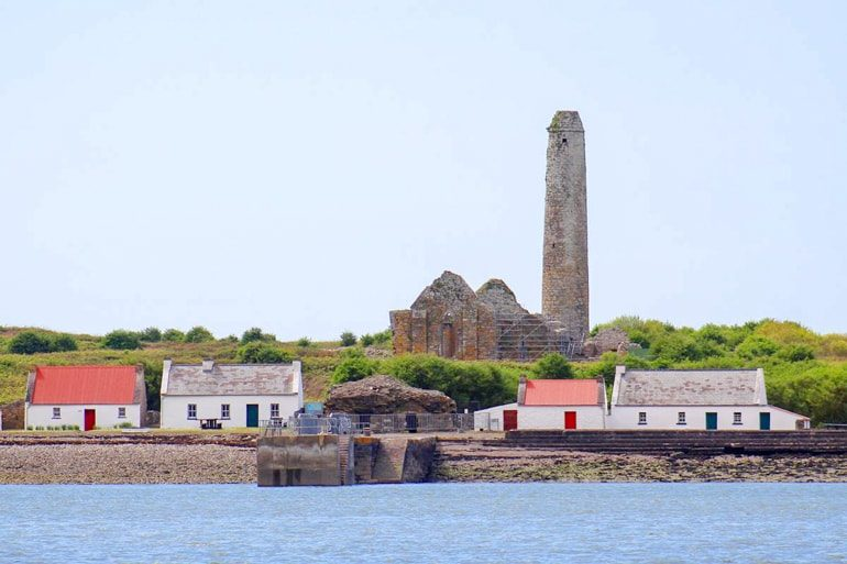 brich chimney and small colourful houses on scattery island with water in front ireland travel tips
