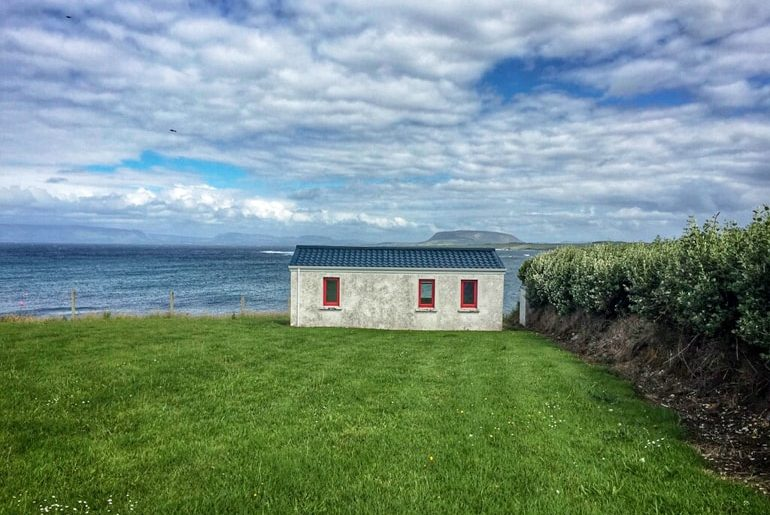 small cottage with green lawn and crashing ocean behind with blue sky ireland travel tips