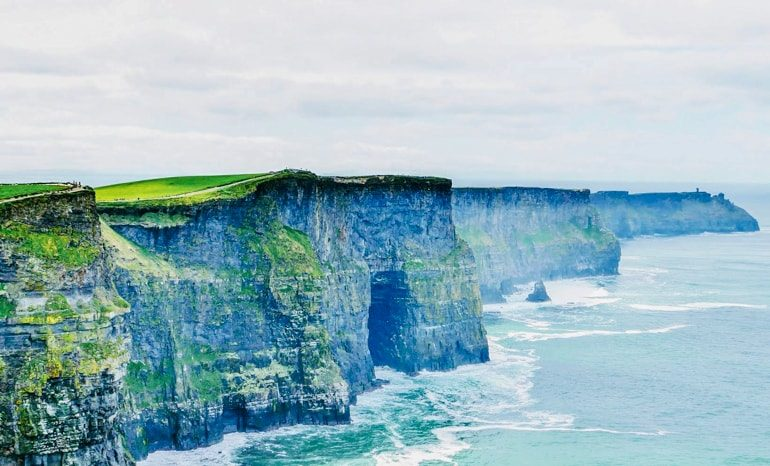 blue green cliffs of moher with waves crashing below in the distance ireland travel tips