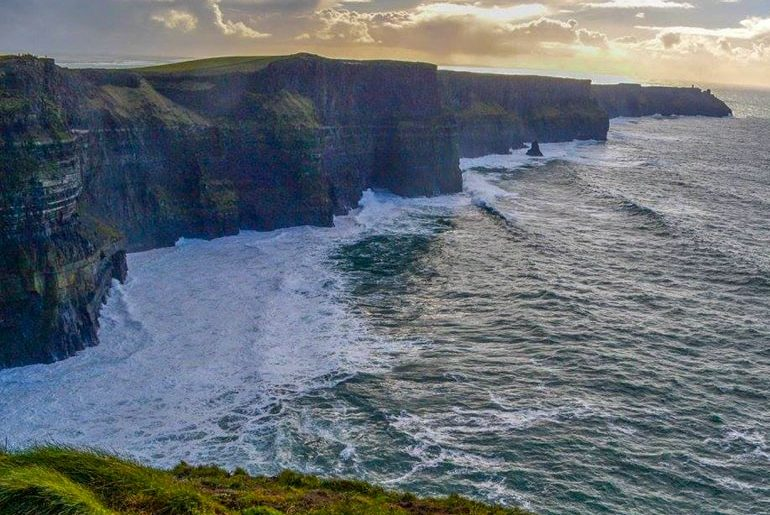 cliffs with water below and sunset above ireland travel tips