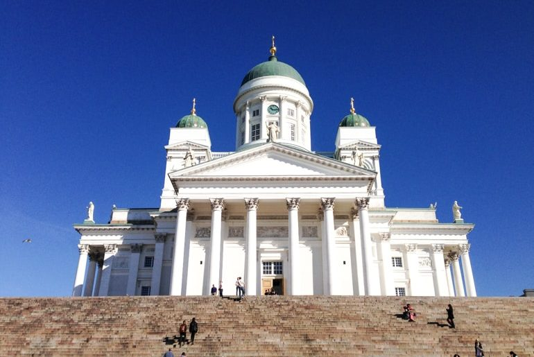 white cathedral with green domes and stairs travelling the baltics