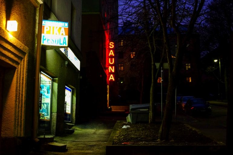 neon sauna sign among helsinki sidewalk at night one day in helsinki
