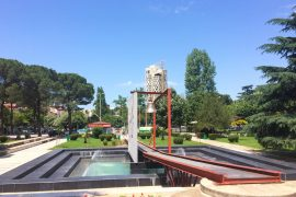 iron bell in green park with pond places to visit in tirana albania