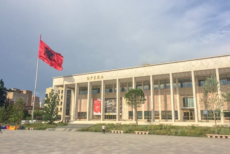 opera house with red albanian flag on pole places to visit in tirana