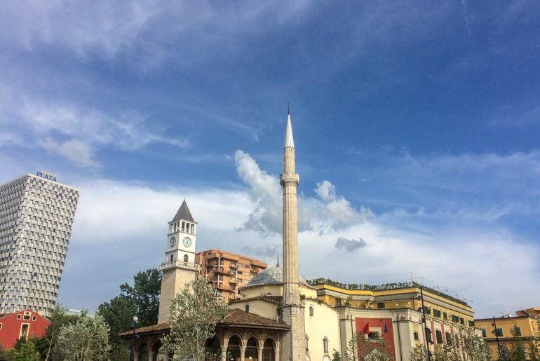 mosque and clock tower with tall building behind and blue sky places to visit in tirana