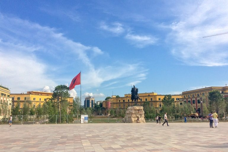 open square with statue and albanian flag and blue sky places to visit in albania
