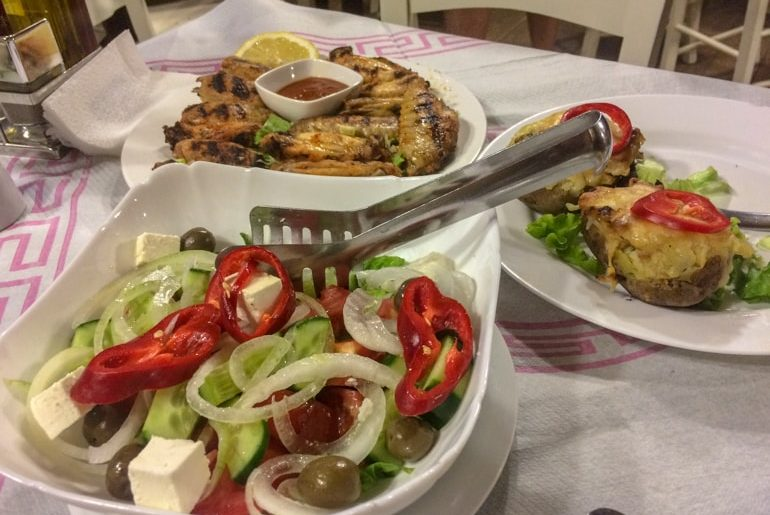 plates of different food like salad and potatoes on table places to visit in tirana