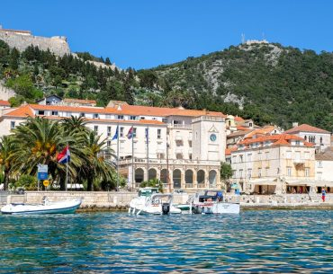 white building with clock and parked boats in front of blue sea and harbour in hvar