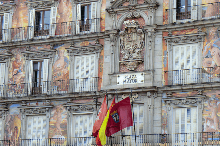 white sign and flag in spanish building in madrid things to do