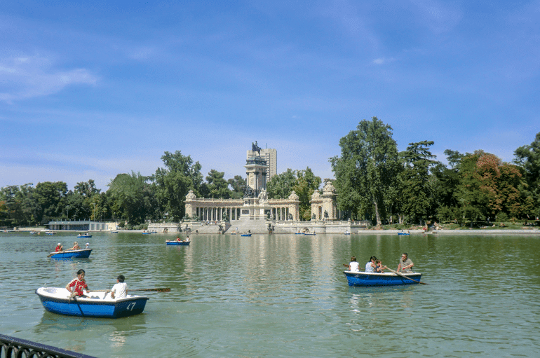 white monument behind row boats on lake in madrid spain attractions