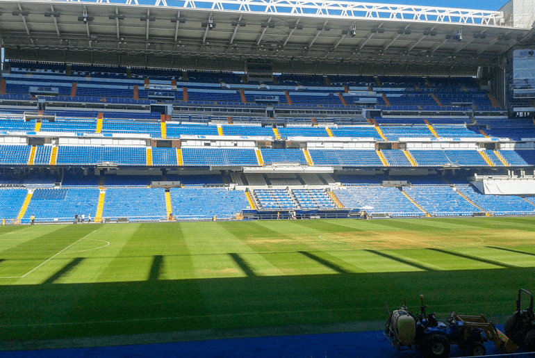 blue seats and green field of madrid football stadium things to do in madrid
